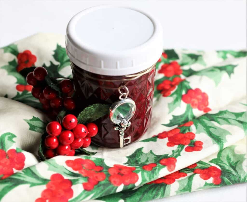 jar of blackberry jam on christmas napking with berries