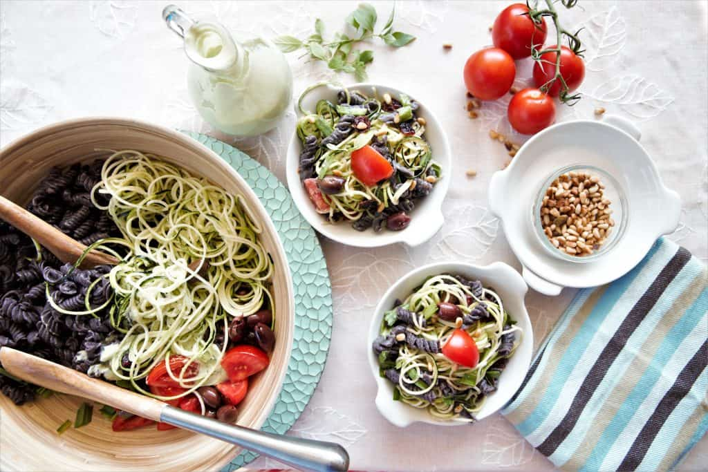large bowl of black bean pasta salad with serving plates