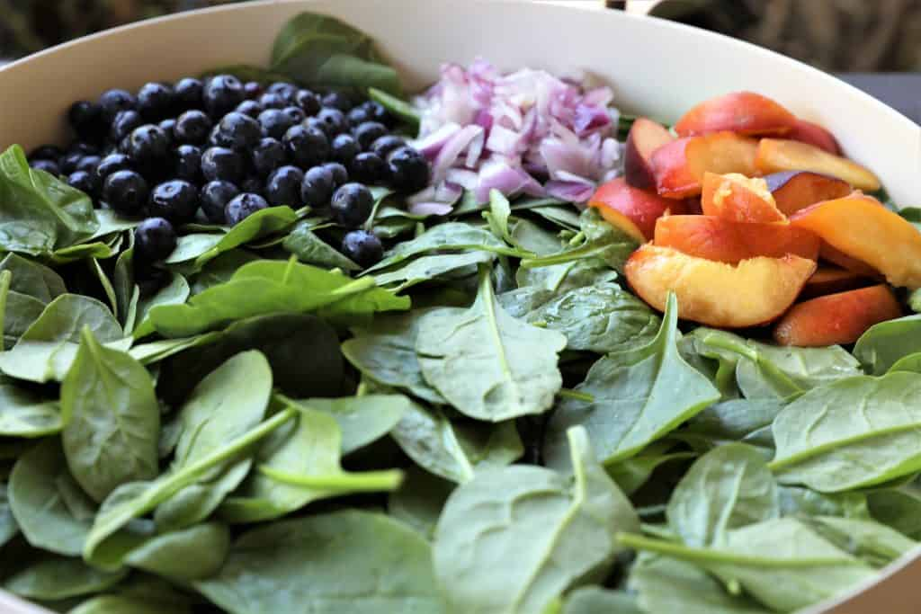 Spread spinach in salad bowl or platter