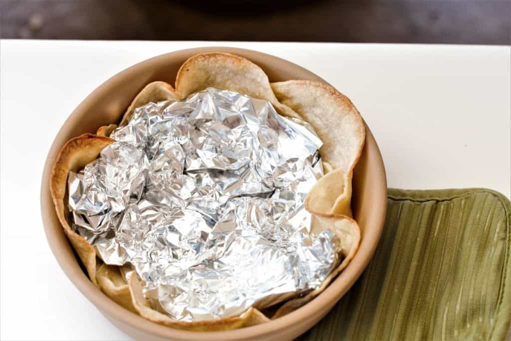 Place corn tortillas in bowl and set with tinfoil. Bake.